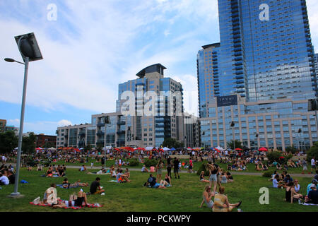 People resting on a lawn next to Smorgasburg in Williamsburg, Brooklyn on JULY 8th, 2017 in New York, USA. (Photo by Wojciech Migda) - Stock Photo