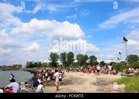 People resting on an East River Park beach during Smorgasburg in Williamsburg, Brooklyn on JULY 8th, 2017 in New York, USA. (Photo by Wojciech Migda) - Stock Photo