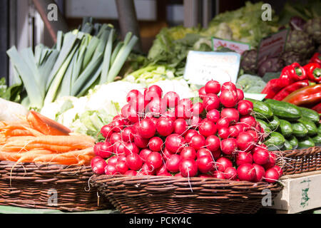 Tasty red radishes in a basket on a farmer market store for presentation with other nutritional organic foods - Stock Photo