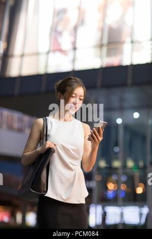 Cheerful young Chinese businesswoman using smart phone - Stock Photo