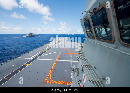 180726-N-VR594-1038 PACIFIC OCEAN (July 26, 2018) Royal Australian Navy landing helicopter dock ship HMAS Adelaide (L01) steams in formation during the Rim of the Pacific (RIMPAC) photo exercise, July 26. Twenty-five nations, 46 ships, five submarines, and about 200 aircraft and 25,000 personnel are participating in RIMPAC from June 27 to Aug. 2 in and around the Hawaiian Islands and Southern California. The world's largest international maritime exercise, RIMPAC provides a unique training opportunity while fostering and sustaining cooperative relationships among participants critical to ensur - Stock Photo