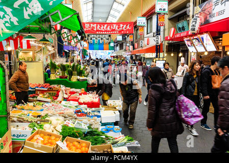 Kuromon Ichiba, Osaka's kitchen food market. View along arcade with various stalls, foreground green grocers. Busy, many people. Winter. - Stock Photo