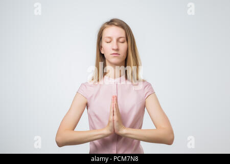 European casually dressed young woman keeping eyes closed while meditating - Stock Photo