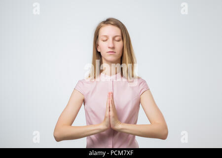 Yoga and meditation. European casually dressed young woman keeping eyes closed while meditating, feeling relaxed during hard working day at office, ho - Stock Photo