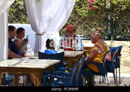 Roquetas de Mar, Almeria, Spain. 3rd Aug, 2018. The heatwave that is hitting Spain is expected to exceed 45°C in some parts of the country. A family of British tourists abroad sit and drink outside in an open air restaurant, a man sits wearing a football shirt. Photo Credit: Paul Lawrenson /Alamy Live News - Stock Photo