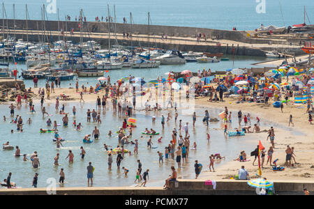 Lyme Regis, Dorset, UK. 3rd August 2018.  UK Weather: Scorching hot sunshine and blue sky in Lyme Regis.  Holidaymakers and sunseekers flock to the packed beach at the seaside resort of Lyme Regis this afternoon as temperatures soar on what is set to be the hottest day on record. Credit: Celia McMahon/Alamy Live News - Stock Photo