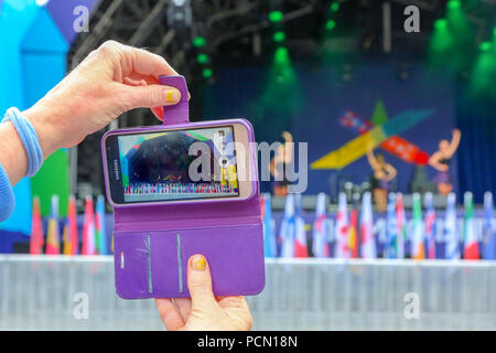 Glasgow, Scotland, UK. 3rd August 2018. Tourists takes a video on her phone of the Scottish Highland Dancing Exhibition taking place in George Square, Glasgow as part of the Glasgow Festival 2018 Credit: Findlay/Alamy Live News - Stock Photo