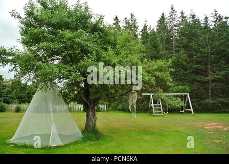 A white mosquito net  under an apple tree and a wooden playset in a backyard with some trees in the background on a cloudy day - Stock Photo