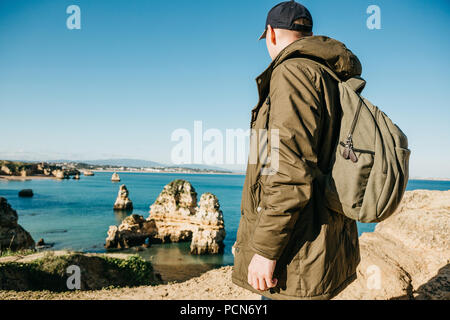 A tourist or traveler with a backpack admires the beautiful view of the Atlantic Ocean and the coast near the city called Lagos in Portugal. - Stock Photo