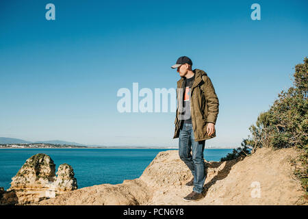 A tourist or traveler with a backpack walks along the coast of the Atlantic Ocean and admires the beautiful view of the ocean near the city called Lagos in Portugal. - Stock Photo