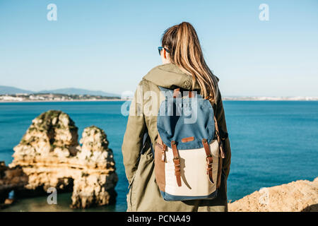 A tourist girl or a traveler with a backpack admiring the beautiful view of the Atlantic Ocean in Portugal. - Stock Photo
