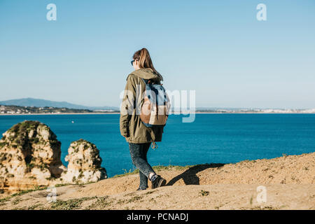A girl tourist or traveler with a backpack walks along the rocky coast and admires the beautiful view of the Atlantic Ocean in Portugal - Stock Photo