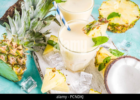 Refreshing summer drink, homemade pina colada cocktail, on a light blue background, with pieces of pineapple, coconut, ice and mint leaves, copy space - Stock Photo