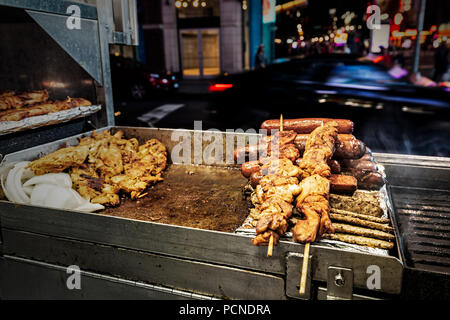 A grill at a food stand in New York City with chicken, sausages and kebabs on skewers. - Stock Photo