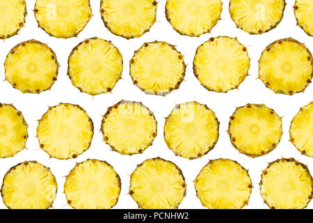 Sliced pineapple pieces lay in pattern on isolated white background.  Freshly cut pineapple fruit - Stock Photo