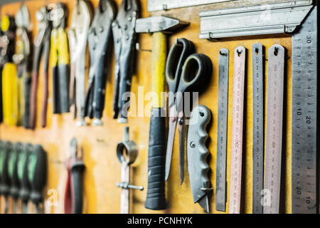 Tools and devices hanging on workshop wall. Rulers, cutting knives, scissors and other objects well arranged in working place. - Stock Photo