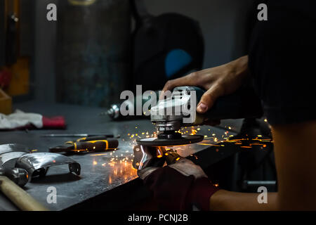 Male metal worker polishing and finalising piece of medieval armour suit. Man hands treating metal parts of hardware in a workshop with angle grinder - Stock Photo