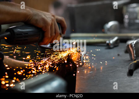 Man hands treating metal parts of hardware in a workshop with angle grinder. Male metal worker polishing and finalising piece of medieval armour suit. - Stock Photo