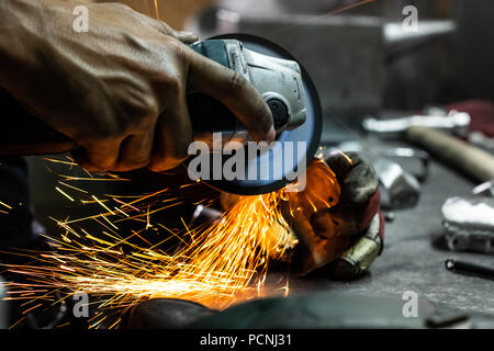 Male metal worker polishing and finalising piece of medieval armour suit. Man hands treating metal parts of hardware in a workshop with angle grinder. - Stock Photo