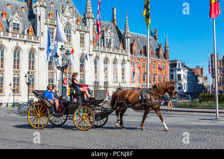 Tourists being taken on a city tour with a horse and trap, Markt Square, Bruges, Belgium - Stock Photo