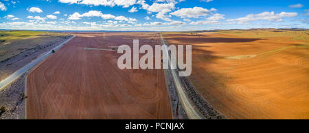 Wide aerial panorama of agricultural fields under beautiful blue sky with white fluffy clouds - Stock Photo