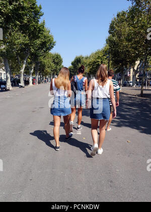 Denim wearing family or friends walking through the Beziers city square - Stock Photo