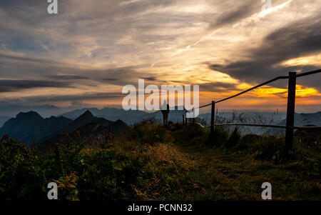 guy silhouette watching at panorama view from a the top of a mountain to lake during sunset, brienzer rothorn switzerland alps - Stock Photo