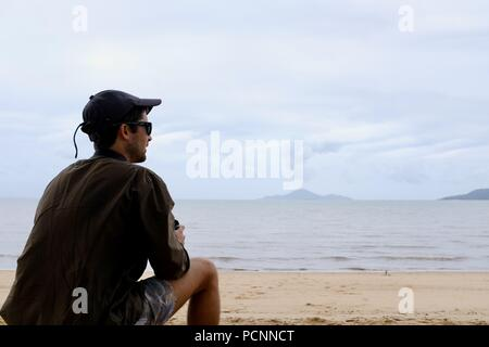A young man sits on a beach, Cardwell, Queensland, Australia - Stock Photo