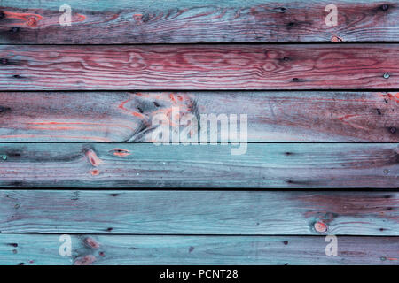 Close-up of the multicolor surface (wall, floor or overhead) made of wooden plank, panel or board in the turquoise, blue, red, claret, coral shades - Stock Photo