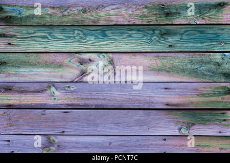 Close-up of the multicolor surface (wall, floor or overhead) made of wooden plank, panel or board in the purple, turquoise, blue, pink, green shades - Stock Photo