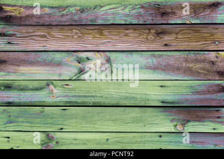 Close-up of the multicolor surface (wall, floor or overhead) made of wooden plank, panel or board in the green, brown, yellow, purple, turquoise shade - Stock Photo