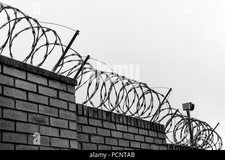 Black and white photo of wall with barbed wire, razor wire, barbwire and camera on the cloudy sky - Stock Photo