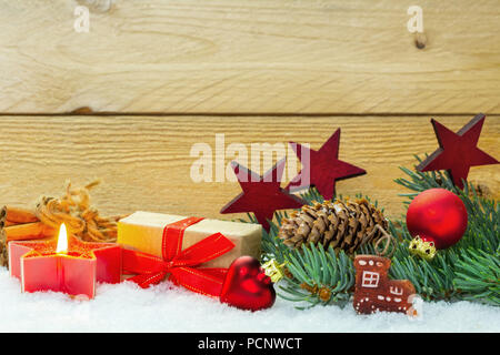Christmas decoration in the snow in front of wood - Stock Photo