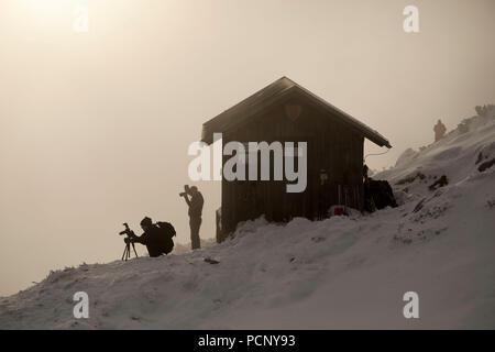 Photographers to the Benediktenwand in front of bivouac hut in winter, Bavarian Alps, Upper Bavaria, Bavaria, Germany - Stock Photo