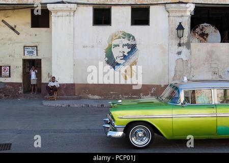 Caribbean, Cuba, Havana, street scene with graffiti of Che and vintage cars