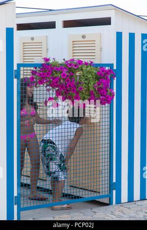 Italy, Santa Margherita Ligure, boy peeping in bathing cabin - Stock Photo