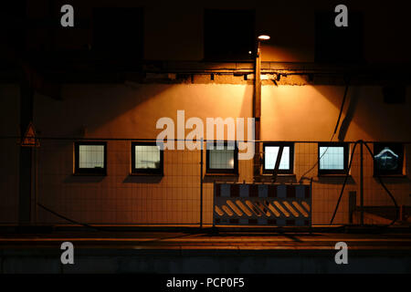 The light beam of a street lamp is falling  at a construction site at a platform at night. - Stock Photo