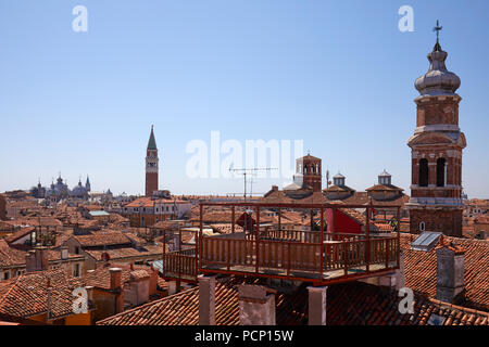 Venice roofs with typical altana balcony and San Marco bell tower in summer, Italy - Stock Photo
