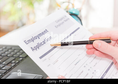 Blank employment application form in hands on a desk - Stock Photo