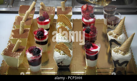 A slection of various cups of ice cream and sweet desserts. - Stock Photo