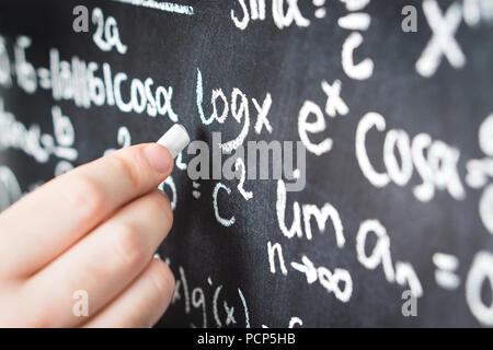Professor writing mathematical formula and equation to blackboard in school classroom. College or university teacher or student with chalkboard. - Stock Photo
