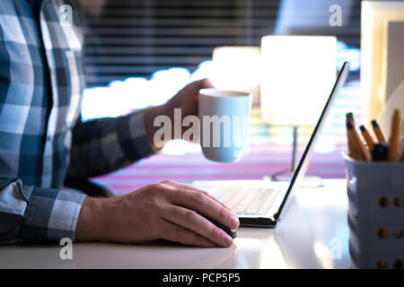 Working late at night and drinking coffee. Man using laptop computer and holding cup or mug in hand in home or office. - Stock Photo