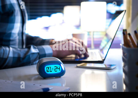 Man working late. Workaholic or being behind schedule concept. Business person in modern office building or home at night using laptop. - Stock Photo