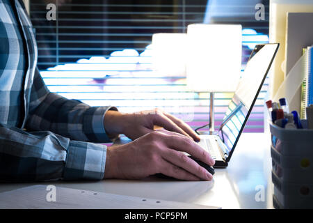 Working late at night, overtime or overwork concept. Man using laptop in modern business office with blurred city background. - Stock Photo