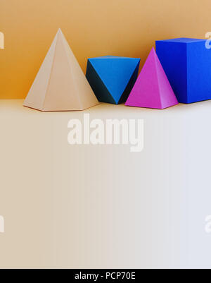 Colorful abstract geometrical composition. Three-dimensional prism pyramid rectangular cube objects on yellow background. Yellow blue pink green colored solid figures. copy space - Stock Photo