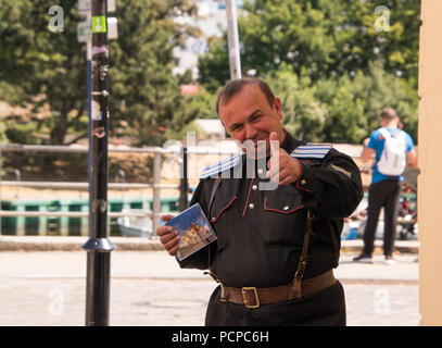 Warmemunde, Germany - June 8, 2018: Middle aged caucasian man with thinning hair in German uniform smiling and giving thumbs up and holding a CD case - Stock Photo