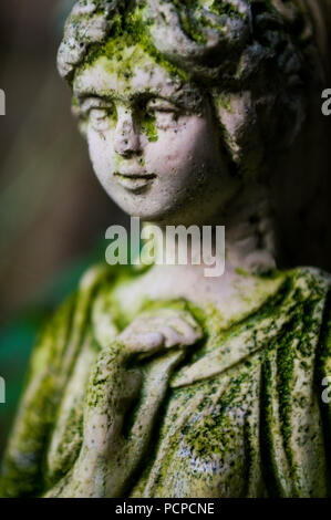 A stone statue of a lady weathered with time - Stock Photo