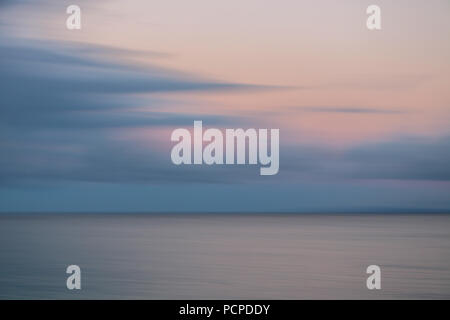 Muted blur sunrise over ocean with pink and gray clouds - Stock Photo