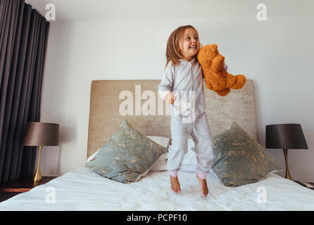 Joyful little girl jumping on bed with teddy bear. Child girl playing on the bed in her bedroom and smiling. - Stock Photo