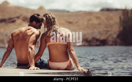 Rear view of loving couple sitting on pier by lake. Man and woman in love having a great time on holiday. - Stock Photo